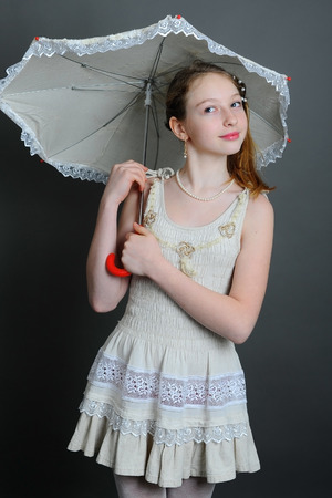 12 13 years: smiling girl 12-13 years standing in studio under an umbrella on a dark background