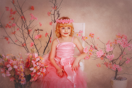 girl in a pink dress sitting on a chair. Wreath on the head and around the flowers. photo