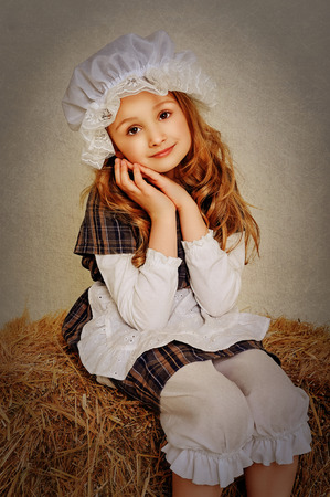 Girl in vintage style rustic sitting on a haystack