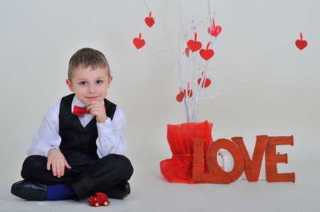 5 6 years: boy with the inscription love sitting near the white tree with red hearts