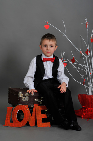 5 6 years: boy sitting on a suitcase with the words love and white tree with red hearts