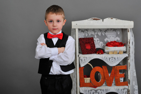 boy in vest, red bow tie. next to the inscription love photo