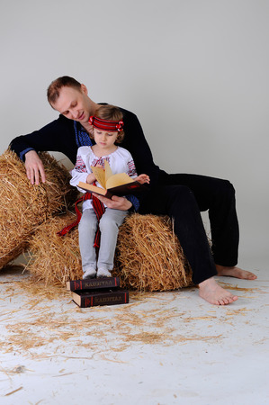 Man and girl in Ukrainian national dress and jeans sitting on a haystack with a book about business in Russian photo