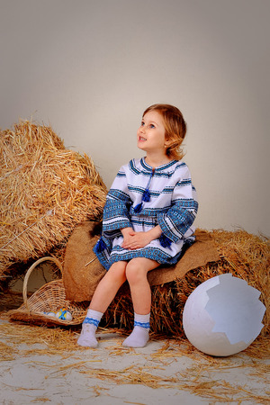 ethnic dress: blond girl in ethnic dress sitting on a bale of hay and looks upwards. It lies next to a large eggshell and eggs in a basket