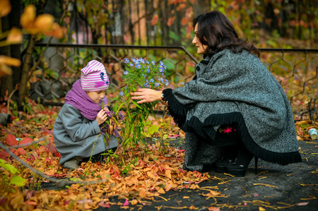 communicates: mother communicates with her daughter and is holding a live flower growing out of soil Stock Photo