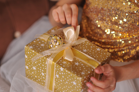 Children's hands open a gift in a gold box with an image of stars with a ribbon