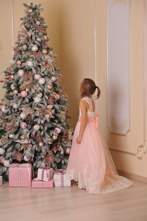 girl in a rose dress stands near the New Year tree with gifts Stock Photo