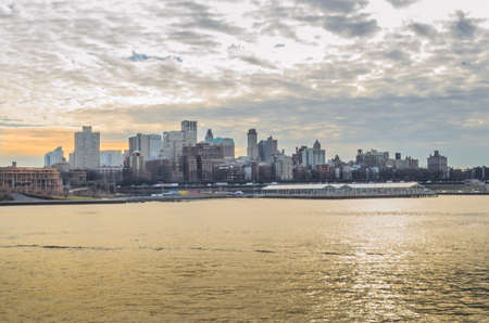 Brooklyn Borough Cityscape at Sunset. Beautiful Colors Reflected in the River and the Clouded Sky. New York City, USA