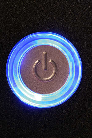 light duty: blue glowing power button - computer or any device is on Stock Photo