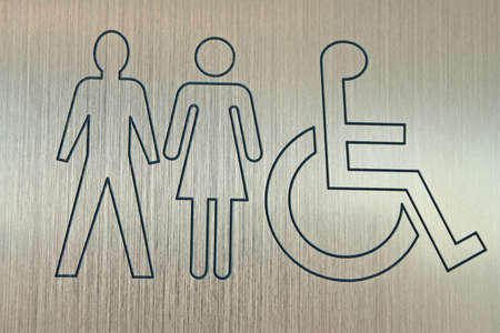 metal sign showing accessible washrooms for men and women photo
