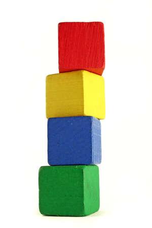 異なる色の 4 つの木製の子供ブロックは高いタワーの高さを強調するために低いカメラ アングルで積み上げ