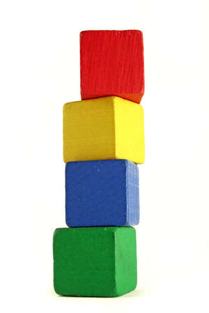 four wooden childrens blocks of different colors stacked in a high tower - low camera angle to emphasize height Banco de Imagens