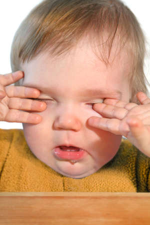 cute very tired baby rubbing eyes with hisher hands photo