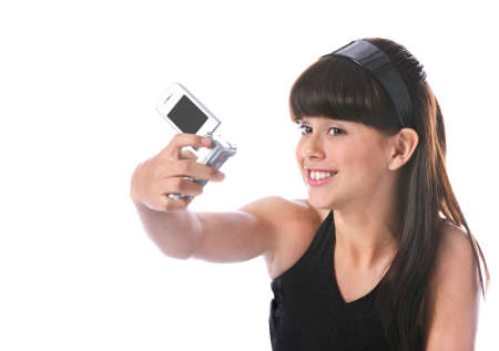 cute girl taking a photo with a camera - phone; isolated on white photo