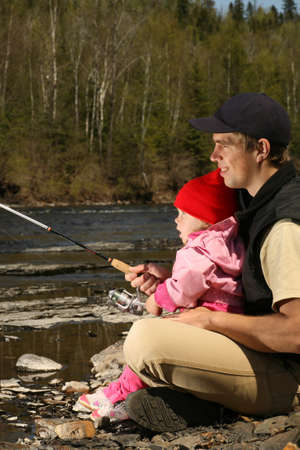 young father teaching his excited little daughter to fish in a rocky river Stock Photo