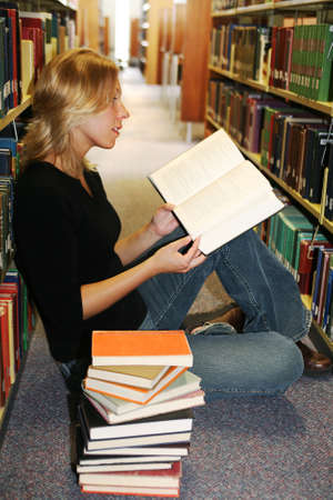 Beautiful young woman sitting on the floor in the library with a stack of books, reading with interest Stock Photo