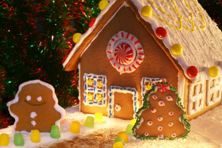 festively lit homemade gingerbread house with snowman, christmas tree and decorations