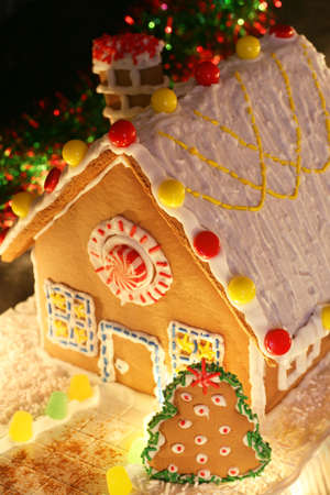 festively: festively lit homemade gingerbread house with christmas tree and decorations
