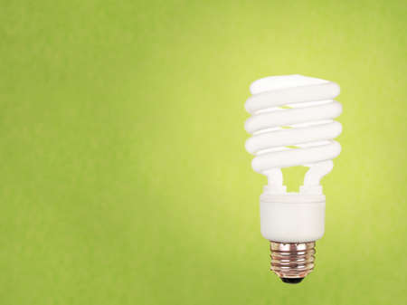 environment friendly: compact fluorescent energy saving environment friendly bulb on green background