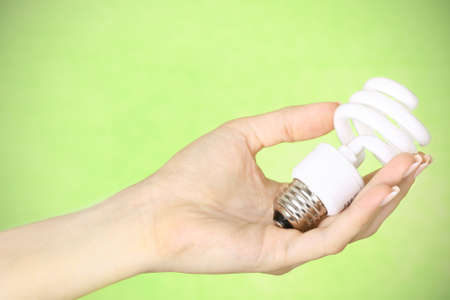 female hand holding a compact fluorescent energy saving environment friendly bulb on green background
