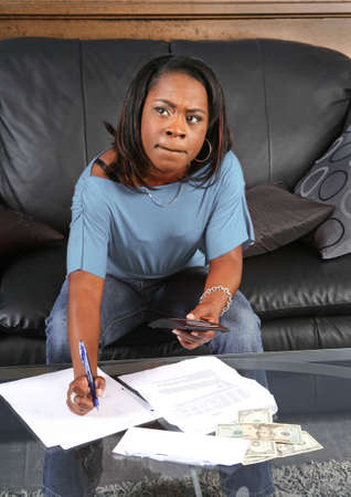 afford: a black woman with a calculator very concerned about big bills