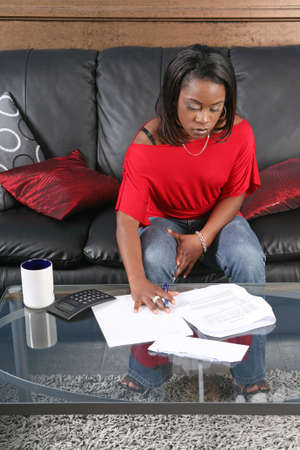 a concerned woman reading a bill or a letter with a pen and a calculator photo