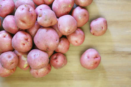 unpeeled: Fresh unpeeled red potatoes spilled on a wooden background Stock Photo