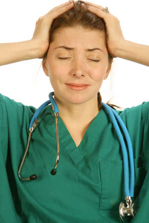 doctor stress: attractive overworked young nurse in green scrubs with a bad headache