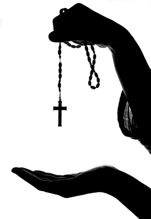rosary beads: hand gives rosary to another hand. religion concept