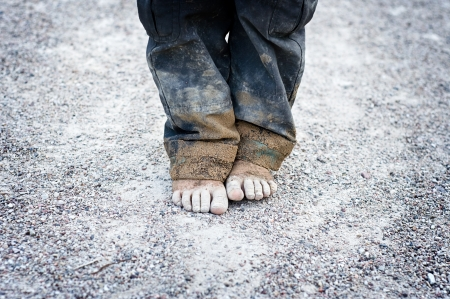 dirty feet: dirty and bare childs feet on gravel. Poverty concept Stock Photo