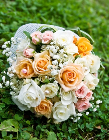 wedding bouquet of roses on green grass.