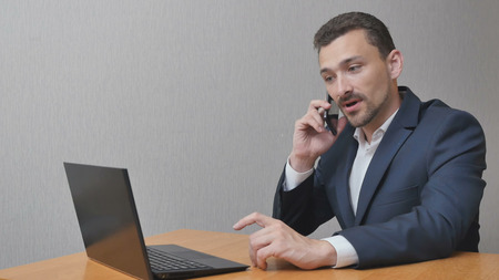 Businessman is finishing a heavy conversation on the phone. The man shakes his head in displeasure and sighs. A person works behind a laptop and has problems