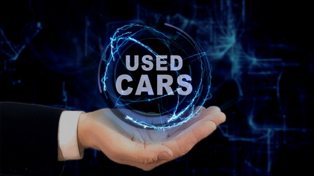 Painted hand shows concept hologram Used cars on his hand. Drawn man in business suit with future technology screen and modern cosmic background Archivio Fotografico