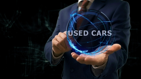 Businessman shows concept hologram Used cars on his hand. Man in business suit with future technology screen and modern cosmic background