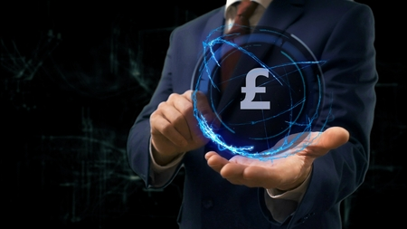 Businessman shows concept hologram Sign British Pound on his hand. Man in business suit with future technology screen and modern cosmic background