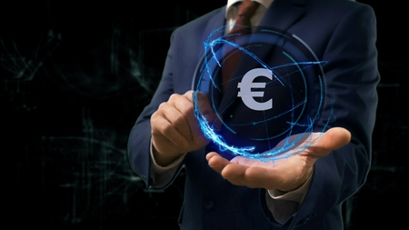 Businessman shows concept hologram Sign EUR on his hand. Man in business suit with future technology screen and modern cosmic background Imagens