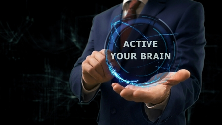 Businessman shows concept hologram Active your brain on his hand. Man in business suit with future technology screen and modern cosmic background