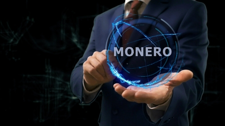 Businessman shows concept hologram Monero on his hand. Man in business suit with future technology screen and modern cosmic background