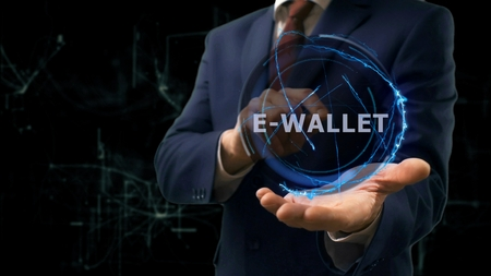 Businessman shows concept hologram E-wallet on his hand. Man in business suit with future technology screen and modern cosmic background