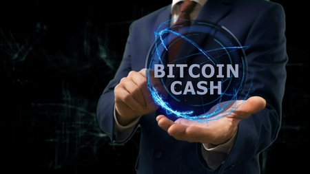 Businessman shows concept hologram Bitcoin cash on his hand. Man in business suit with future technology screen and modern cosmic background Imagens