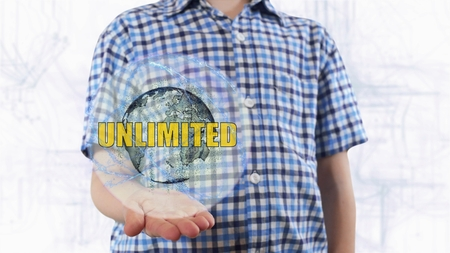Young man shows a hologram of the planet Earth and text Unlimited. Boy with future technology 3d projection on a modern white digital background