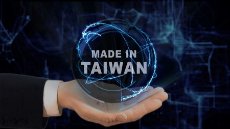 Painted hand shows concept hologram Made in Taiwan on his hand. Drawn man in business suit with future technology screen and modern cosmic background Stock Photo