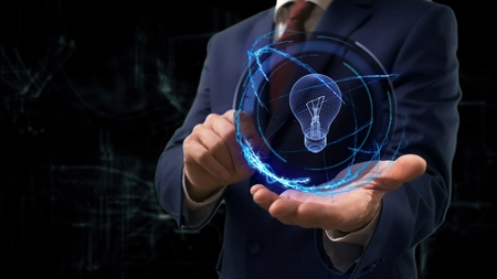 Businessman shows concept hologram 3d Bulb Lamp on his hand. Man in business suit with future technology screen and modern cosmic background 免版税图像 - 106827320