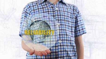 Young man shows a hologram of the planet Earth and text Reliability. Boy with future technology 3d projection on a modern white digital background