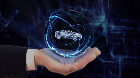 Painted hand shows concept hologram 3d sport car on his hand. Drawn man in business suit with future technology screen and modern cosmic background