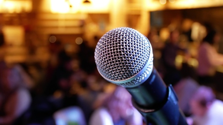 Microphone on the background of the hall with people with blurred bokeh Stockfoto