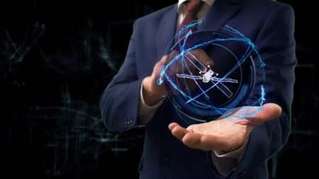 Businessman shows concept hologram 3d Satellite on his hand. Man in business suit with future technology screen and modern cosmic background