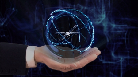 Painted hand shows concept hologram 3d Satellite on his hand. Drawn man in business suit with future technology screen and modern cosmic background