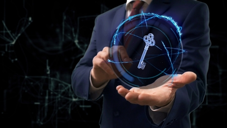 Businessman shows concept hologram 3d key on his hand. Man in business suit with future technology screen and modern cosmic background Stockfoto