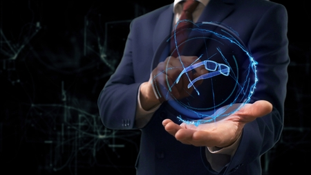 Businessman shows concept hologram 3d glasses on his hand. Man in business suit with future technology screen and modern cosmic background